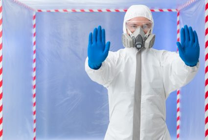 close-up of man wearing white protection suit, gas mask and rubber gloves, stop gesture